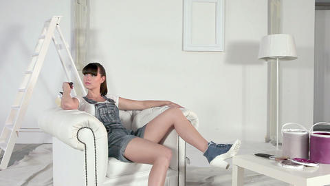 Young woman sitting in armchair with painting equipment Stock Video Footage