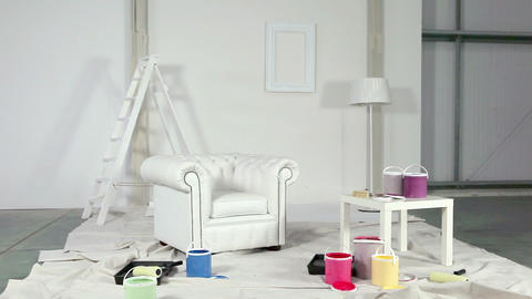 White armchair and painting equipment in room Stock Video Footage