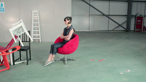 Young woman on swivel chair with pile of chairs Stock Video Footage
