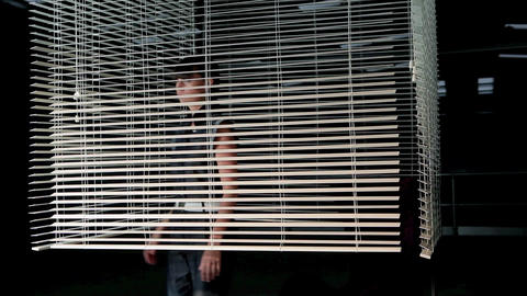 Young woman peering though venetian blind Stock Video Footage