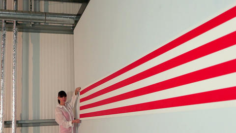 Young woman pulling striped wallpaper along wall Stock Video Footage