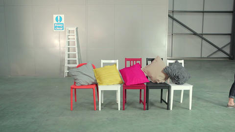 Young woman placing cushions on chairs Stock Video Footage