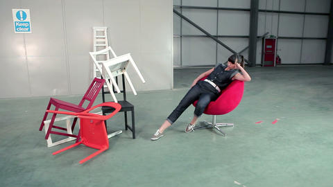 Young woman in swivel chair kicking pile of chairs over Stock Video Footage