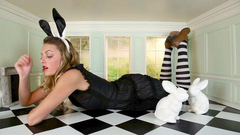 Young woman in small room with bunny ears and rabbit figures Stock Video Footage