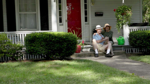 Senior couple sitting on front stoop Stock Video Footage