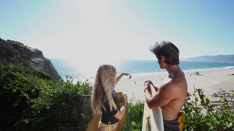 Surfer couple looking down to sea from above Stock Video Footage