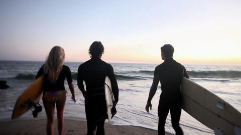 Camera following three surfers as they go into the sea Stock Video Footage