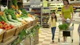 Mother and children in fruit and vegetable section of supermarket Footage