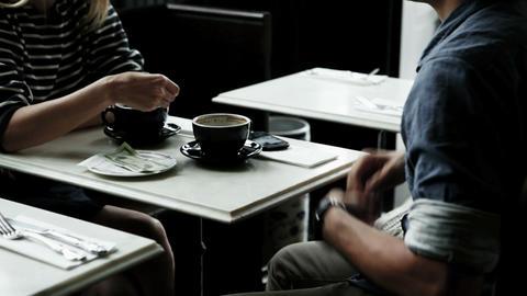 Couple having coffee, man pays bill Stock Video Footage