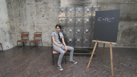 Young woman writing e=mc2 on blackboard then sitting down Stock Video Footage