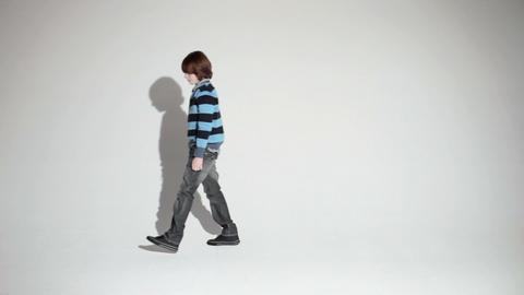 Boy sitting in studio and walking away Stock Video Footage