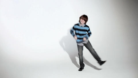 Boy doing silly dance past camera Stock Video Footage