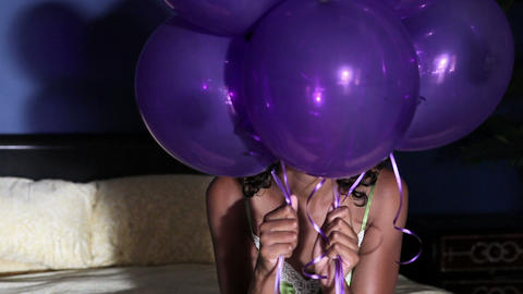 Young woman on bed, holding balloons Stock Video Footage