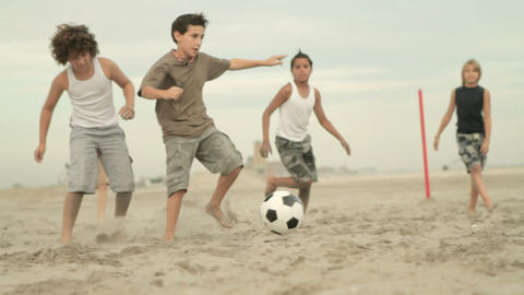 Boys playing game of football on beach Stock Video Footage