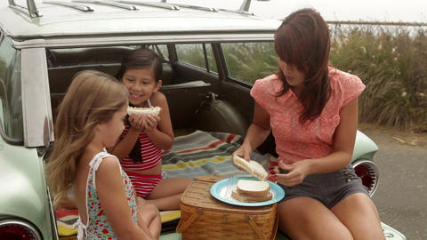 Mother and daughters sitting on car eating sandwiches Stock Video Footage
