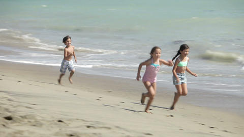 Three children running along water's edge Stock Video Footage