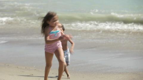 Three children running along water's edge Stock Video Footage