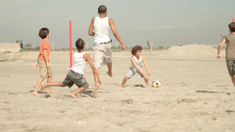 Boys playing football on beach, kick off Stock Video Footage