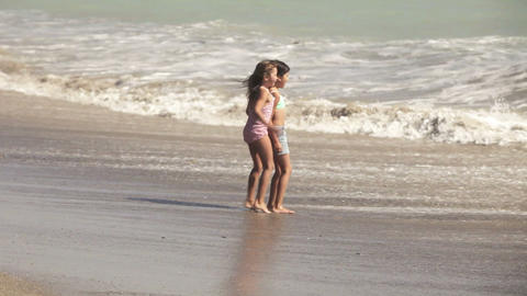 Two girls running into sea and waves Stock Video Footage
