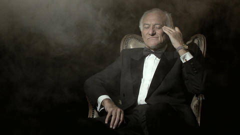 Senior man in a dinner jacket, smoking a cigar Stock Video Footage
