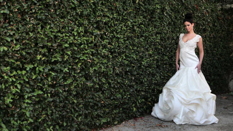 Woman by hedge wearing white wedding dress Stock Video Footage