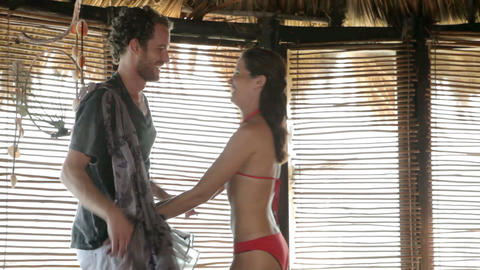 Couple undressing and kissing in beach hut on vacation Stock Video Footage