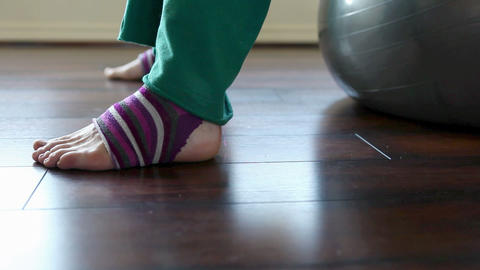 Woman wearing striped leg warmers on pilates ball Stock Video Footage
