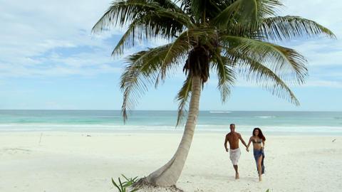 Couple running on sandy beach Stock Video Footage