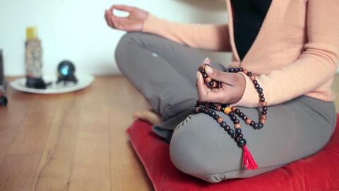 Woman sitting cross legged, meditating with beads Stock Video Footage