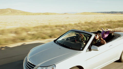 Three young women driving along in convertible car Stock Video Footage