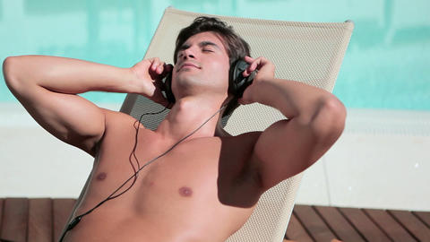 Man listening to music on headphones on sunlounger Stock Video Footage