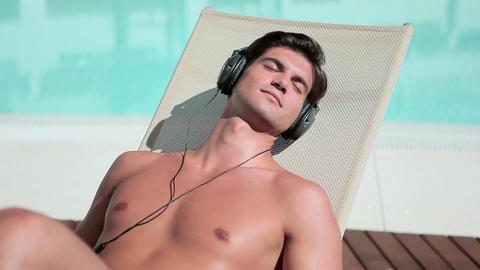 Man listening to music on headphones on sunlounger Stock Video Footage