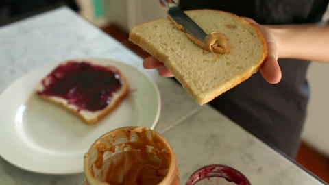 Close up of child making peanut butter and jelly sandwich Stock Video Footage