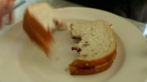 Person placing half eaten sandwich on plate Stock Video Footage