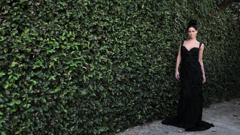 Woman by hedge wearing black evening gown Stock Video Footage