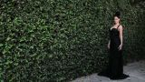 Woman by hedge wearing black evening gown Footage