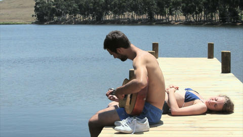 Couple sitting on jetty, man playing guitar Stock Video Footage