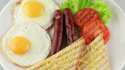 English breakfast with fried eggs, sausages, toasts and fresh salad Footage
