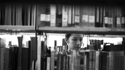 Female, Asian Girl Student Walking Between Shelves, Searching For Books In Black stock footage