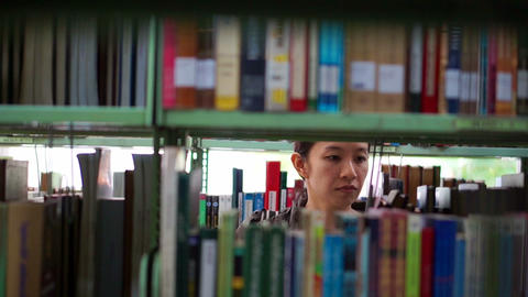 Girl Asian student walking between shelves, searching for books Footage