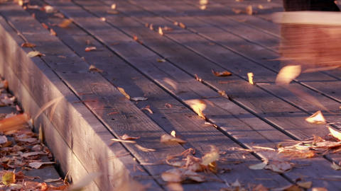 Sweeping dried autumn leaves at a wooden balkony Footage