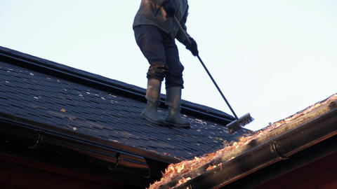 Timelapse shot of man sweeping dried leaves on a roof Footage