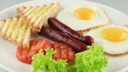 breakfast with fried eggs, sausages, toasts and tomatoes on white plate Footage