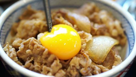 Delicious eating raw egg yolk on food. Japanese beef over rice. Poached runny eg Footage