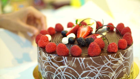 unwrapping sticky chocolate cake with fresh strawberries and berries Live Action