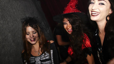 Three girls in costumes at Halloween party. Red witch, skeleton, leather dress Footage