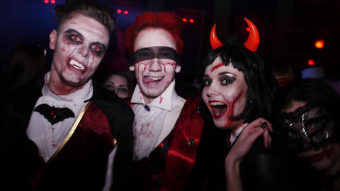 People in costume at Halloween party. Two bloody scary vamp, devil girl. Red eye Footage