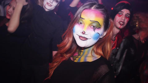 Girl with colorful painted face at Helloween patry in nightclub. Puppy Footage