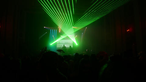 Green beams from floodlights in crowded nightclub . Audience. Laser show Footage
