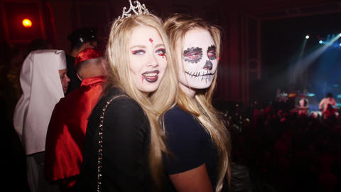Girls with grimm on face dance at Halloween party in club. Mask, vamp, skeleton Live Action